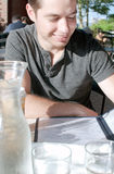 Lächelndes Mannlesemenü im Restaurant Stockfoto