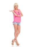 Lächelndes Modemädchen, das Produkt darstellt Lizenzfreie Stockfotografie