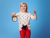 Lächelndes modernes Mädchen, das Wecker und Spritze auf Blau zeigt Lizenzfreies Stockfoto