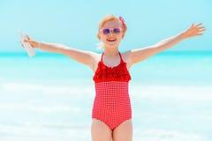 Lächelndes modernes Mädchen mit Sonnenschutz freuend auf Seeküste stockfotografie