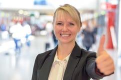Lächelndes motiviertes Frauengeben Daumen oben Stockfotografie