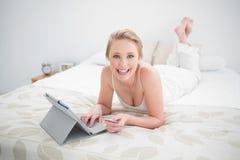 Lächelndes natürliches blondes Lügen auf Bett und Anwendung der Tablette Stockbild