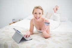 Lächelndes natürliches blondes Lügen auf Bett und Anwendung der Tablette und der Kreditkarte Stockbild