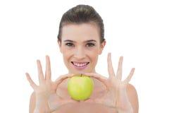 Lächelndes natürliches braunes behaartes Modell, das einen Apfel hält Lizenzfreies Stockbild