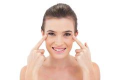 Lächelndes natürliches braunes behaartes Modell, das ihre Augen mit ihren Fingern zeigt Stockfoto