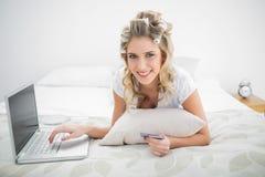 Lächelndes nettes blondes Einkaufen online unter Verwendung des Laptops Lizenzfreie Stockbilder