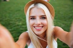 Lächelndes nettes blondes Mädchen der Junge im Hut, der selfie macht Stockfotografie