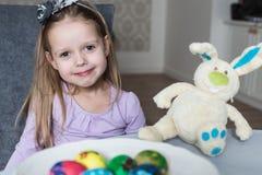 Lächelndes nettes Kind mit Ostereiern und Plüschhäschen ostern Lizenzfreie Stockfotografie