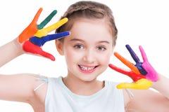 Lächelndes nettes kleines Mädchen mit den gemalten Händen. Stockbild