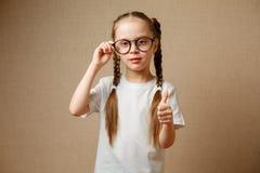 lächelndes nettes kleines Mädchen mit den schwarzen Brillen, die sich Daumen zeigen stockfoto