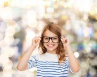 Lächelndes nettes kleines Mädchen mit schwarzen Brillen Lizenzfreie Stockfotografie