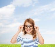 Lächelndes nettes kleines Mädchen mit schwarzen Brillen Stockfotos