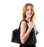 Lächelndes nettes Mädchen mit schwarzer Handtasche Stockfotografie