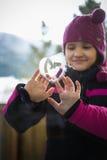 Lächelndes nettes Mädchenzeichnungsherz auf Fenster Stockbild