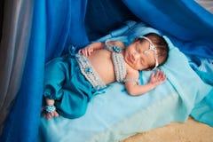 Lächelndes neugeborenes Baby, das ein Bauchtanz-Kostüm trägt stockfoto