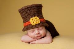 Lächelndes neugeborenes Baby, das einen Pilger-Hut trägt stockfotos