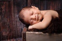 Lächelndes neugeborenes Baby, das in einer rustikalen Kiste schläft stockfotos