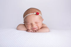 Lächelndes neugeborenes Baby, das rote Rose Headband trägt lizenzfreies stockfoto
