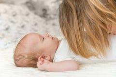 Lächelndes neugeborenes Baby und Mutter Stockfotografie
