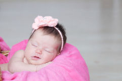 Lächelndes neugeborenes Schlafen im Korb mit gestrickter Blume auf Kopf, Baby, das auf rosa Decke, nettes Kind liegt Stockbilder