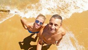 Lächelndes Paar macht ein selfie auf dem Strand Stockbild