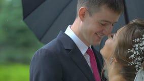 Lächelndes Paar von Jungvermählten in der Liebe reibt zart Nasen unter dem Regenschirm im Regen Nahaufnahmeseitenporträt stock footage