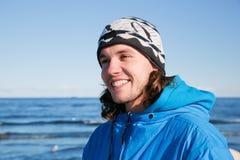 Junges glückliches Mannporträt auf dem Strand. Kalter sonniger Tag Lizenzfreie Stockfotografie