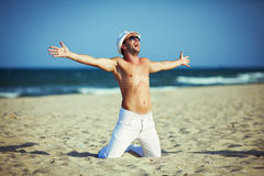 Lächelndes Porträt des Mannes sitzend auf dem Strand Stockfotografie