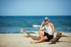 Lächelndes Porträt des Mannes sitzend auf dem Strand Lizenzfreie Stockfotografie