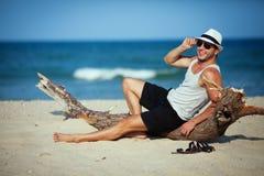 Lächelndes Porträt des Mannes sitzend auf dem Strand Lizenzfreie Stockfotos