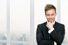 Lächelndes rührendes Gesicht des Managers gegen Fenster Lizenzfreie Stockbilder