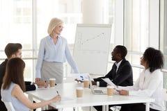 Lächelndes reifes Geschäftsfraugriff-Geschäftstreffen mit jungem EM stockfoto