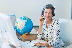 Lächelndes Reisebüro, das an ihrem Schreibtisch sitzt Stockfotografie