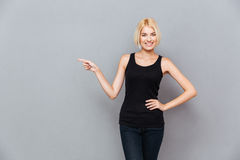 Lächelndes reizendes junges womanwith blondes Haar, das weg zeigt Lizenzfreie Stockfotos