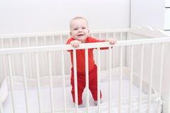 Lächelndes reizendes 6-monatiges Baby, das im weißen Bett steht Stockbild