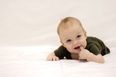 Lächelndes Säuglingskind, das auf der weißen Decke liegt Lizenzfreies Stockfoto