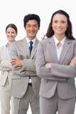 Lächelndes salesteam, das mit den gefalteten Armen steht Stockbild