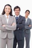 Lächelndes salesteam, das zusammen mit gefalteten Armen steht Stockbilder
