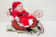 Lächelndes Schätzchen im WeihnachtsPferdeschlitten stockfoto