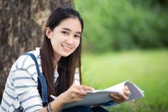 Lächelndes schönes asiatisches Mädchenlesebuch und -funktion am Baum an stockfotografie