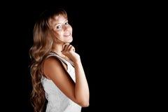 Lächelndes schönes blauäugiges blondes Mädchen im weißen Kleid auf einem schwarzen Hintergrund Lizenzfreies Stockfoto