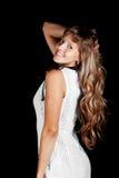 Lächelndes schönes blauäugiges blondes Mädchen im weißen Kleid auf einem schwarzen Hintergrund Stockfotos
