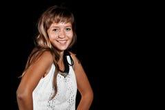 Lächelndes schönes blauäugiges blondes Mädchen im weißen Kleid auf einem schwarzen Hintergrund Lizenzfreie Stockbilder