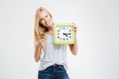 Lächelndes schönes blondes Mädchen, das Finger auf Wanduhr zeigt Lizenzfreie Stockfotografie