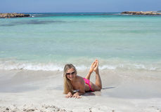 Lächelndes schönes blondes Mädchen liegen auf dem Strand Stockfoto