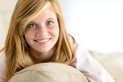 Lächelndes schönes Jugendlichmädchen, das auf Kissen liegt Stockfotos