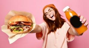 Lächelndes schönes junges blondes Frauenmodell im Hippie Hoodiestoff-Holdinghamburger und im Flaschensaft stockfoto