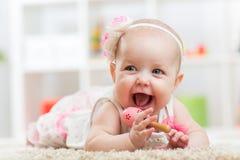Lächelndes schönes Kindermädchen liegt mit Spielzeug an Stockbilder
