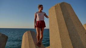 Lächelndes schönes Mädchen, das auf Betonblöcken vor dem Meer steht stock footage