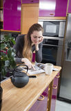Lächelndes schönes Mädchen, das eine Zeitschrift auf ihrer Küchenarbeitsplatte liest Stockbilder